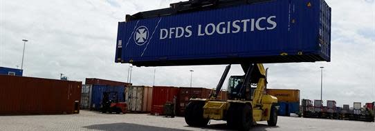 DFDS Logistics loader in a shipyard hoisting a DFDS container