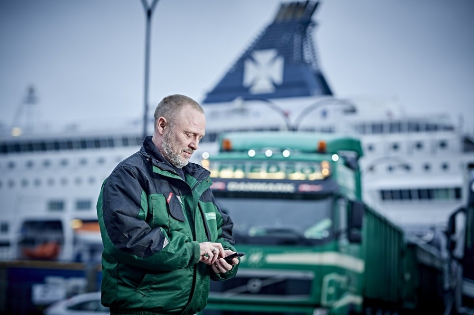 DFDS Logistics truck driver with a mobile phone