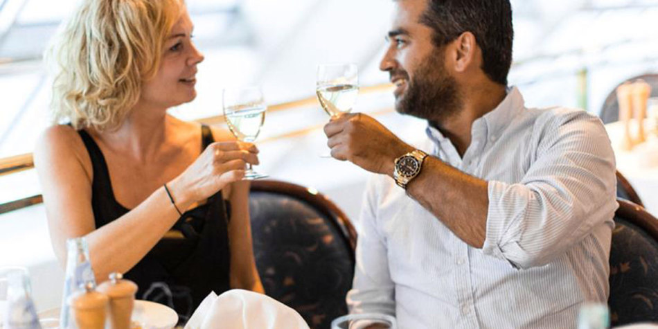 A couple toasting with white wine at onboard restaurant