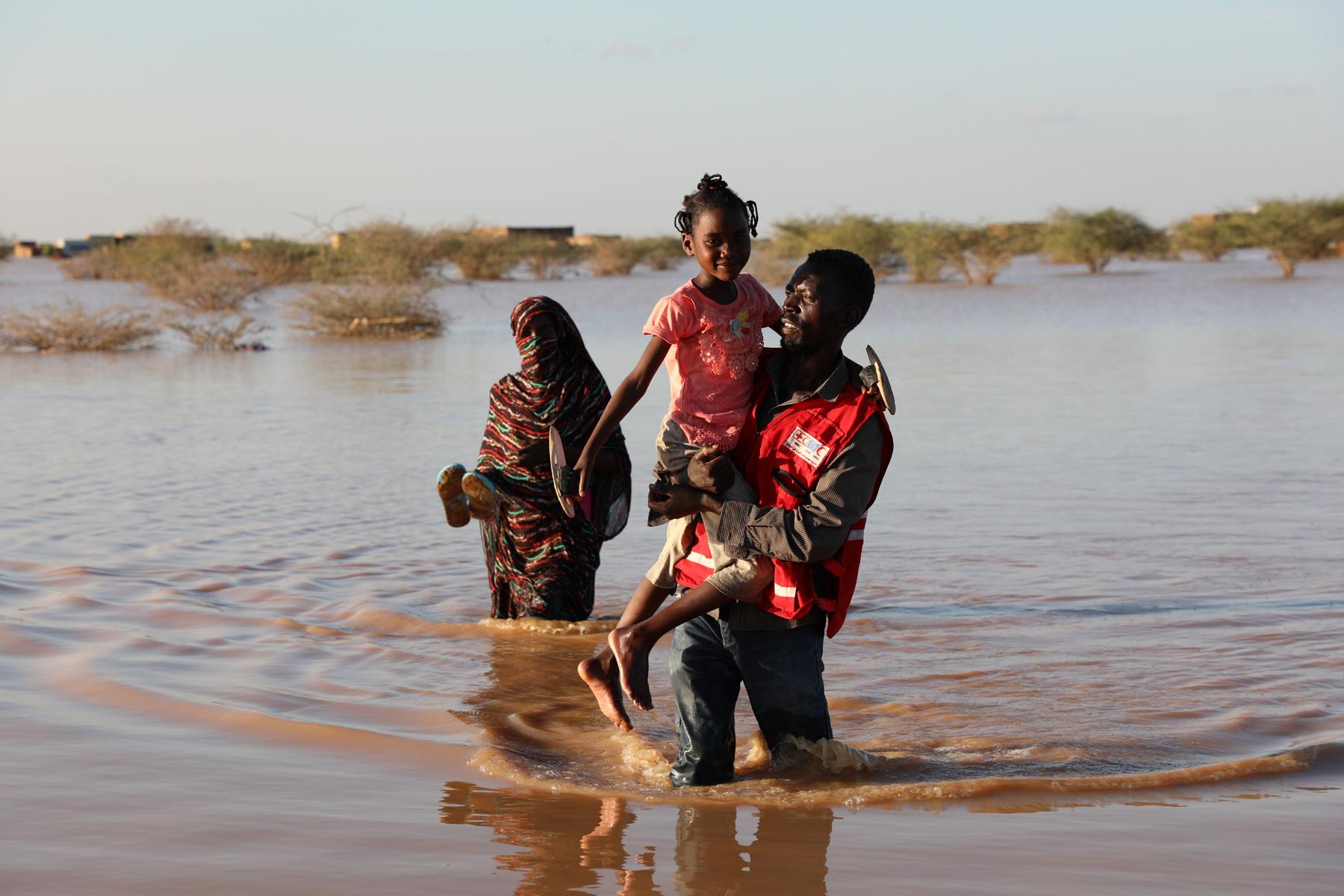 Un bénévole du Croissant-Rouge soudanais porte secours à une femme et à son enfant. © Haitham Ibrahim, SRCS