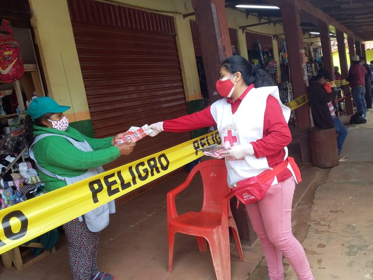 Eine Freiwillige des Roten Kreuzes informiert eine Marktfrau über die Abstands- und Hygieneregeln. © Cruz Roja Boliviana
