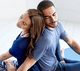 A couple is sitting on the floor, they sit back to back with eyes closed.
