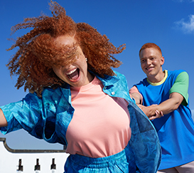 A couple with ginger hair is holding each other - a woman is laughing and a man is smiling.
