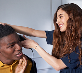 Young woman is trimming hair of young man who is sitting.