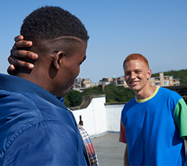 Two young men looking at each other - a man in the foreground is standing backwards and touching his head.