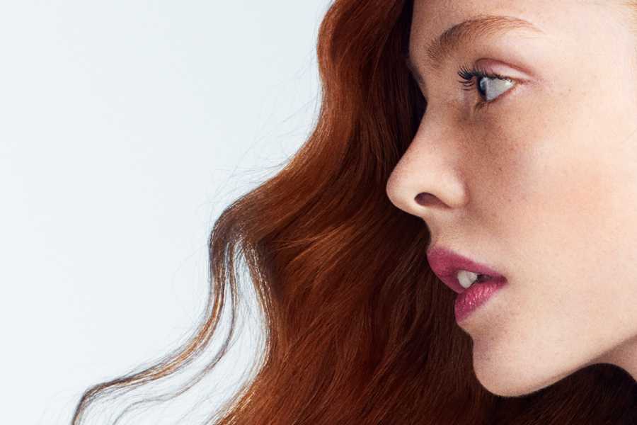 Woman with red flowing hair looks to the side