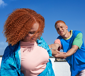 A couple with ginger hair is holding each other - a woman is smiling and a man is holding her hand.