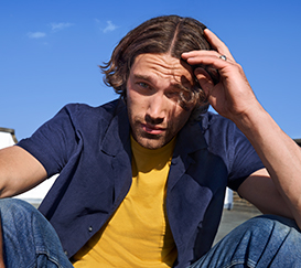 A man with middle-length hair is touching up his hair.
