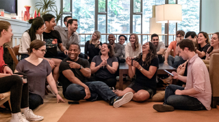 alt text Group of Justworks employees gathering together as they bond and laugh