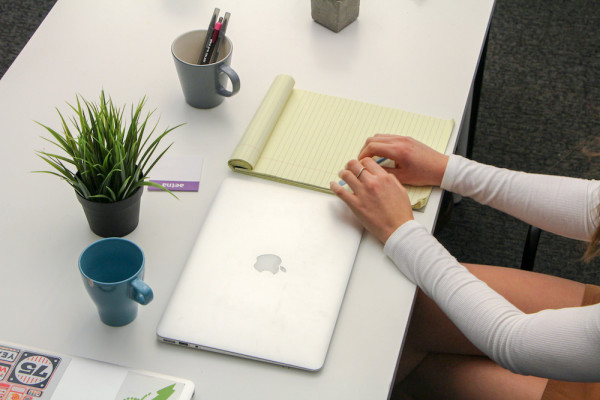 woman at desk with notepad and laptop