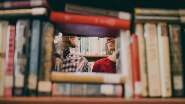 people talking in a library with books