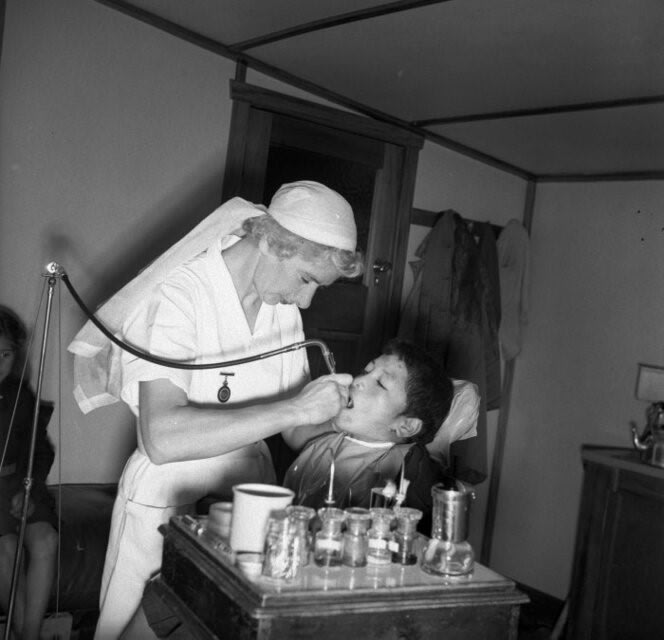 dental nurse giving a boy treatment 1944