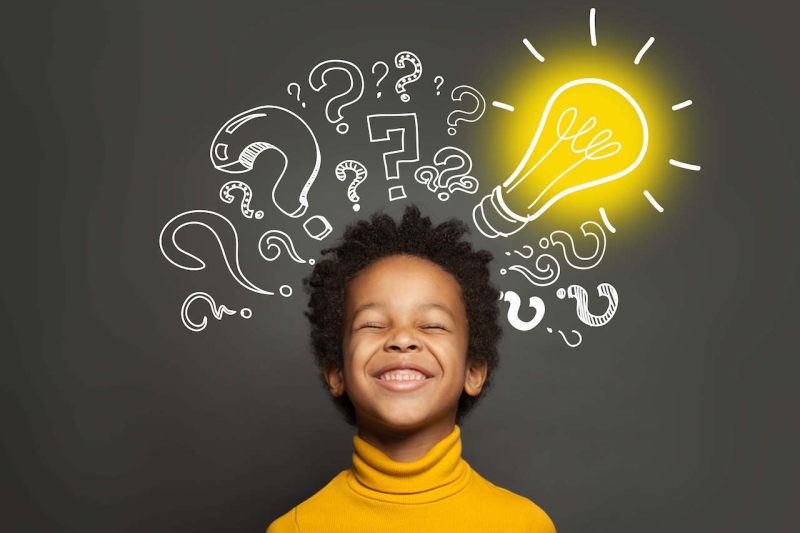 A child with question marks and a light bulb overhead, showing his computational thinking