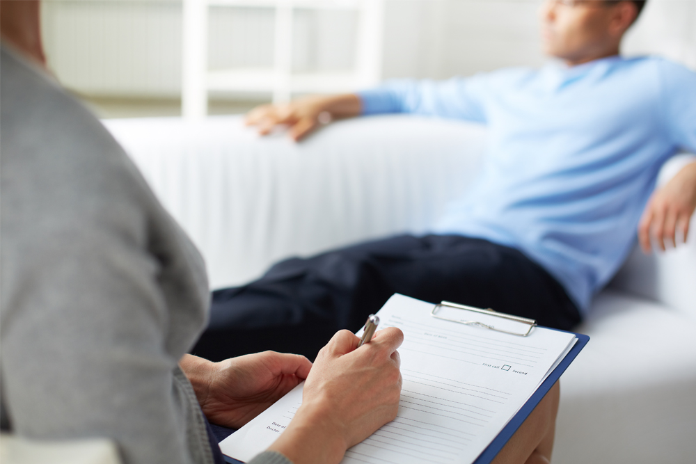 A man seated in a therapist's office while she takes notes