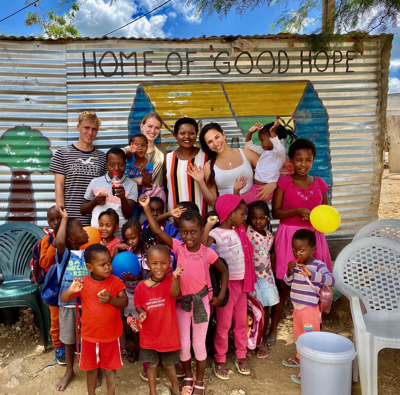 Einige Kinder von Home of Good Hope stehen zusammen mit Monica und Leonie und Kaja vor der Kamera und lächeln in die Kamera.
