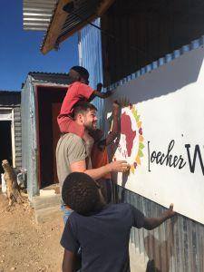 Auf dem Bild ist ein Volunteer zusammen mit einigen Schülern der Preschool zu sehen. Gemeinsam streichen Sie das neue Klassenzimmer von Monika.