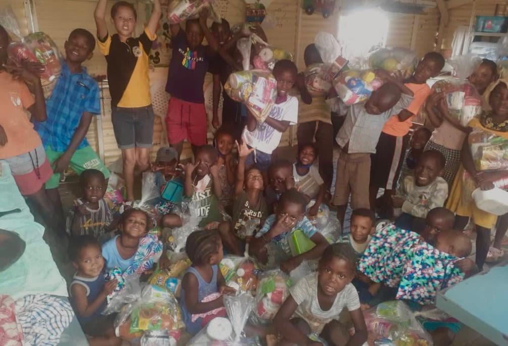 Auf dem Foto befinden sich eine Gruppe von über 20 Kindern in Monicas Soup Kitchen und halten kleine Säcke mit Lebensmitteln, Zahnpasta und Klamotten in die Luft.