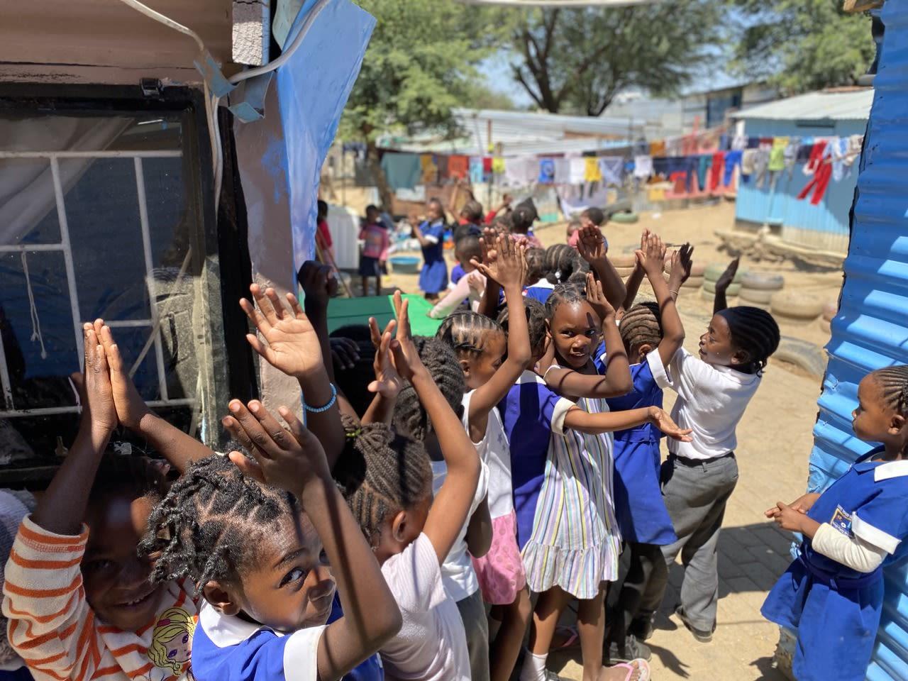 Kinder stehen in ihrer blauen Schuluniform in langer Schlange und klatschen freudig in die Hände.