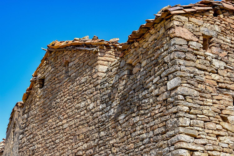 Zu sehen ist die grau braune Mauer eines Steinhauses vor einem hellblauen Himmel.