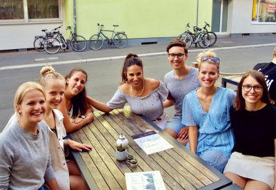 Eine Gruppe junger Menschen sitzen an einem Tisch in einem Cafe und lächeln in die Kamera.