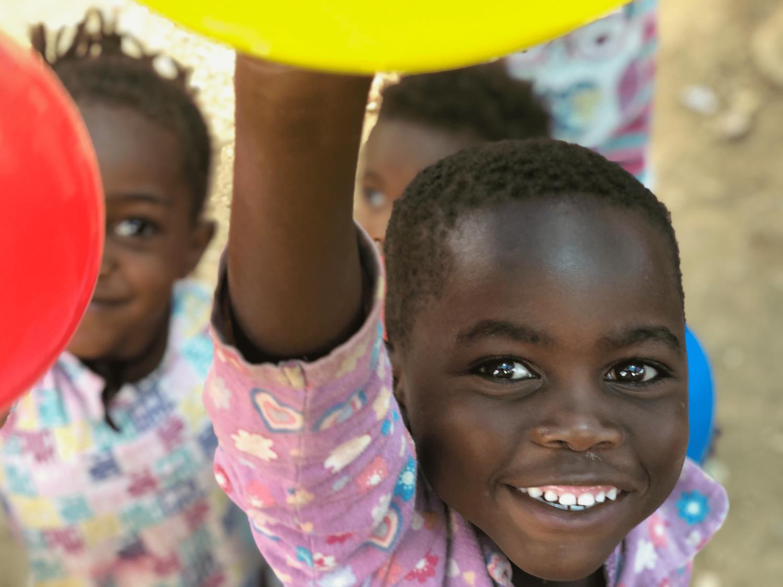Ein kleiner Junge hält glücklich einen großen gelben Luftballon in das Bild.
