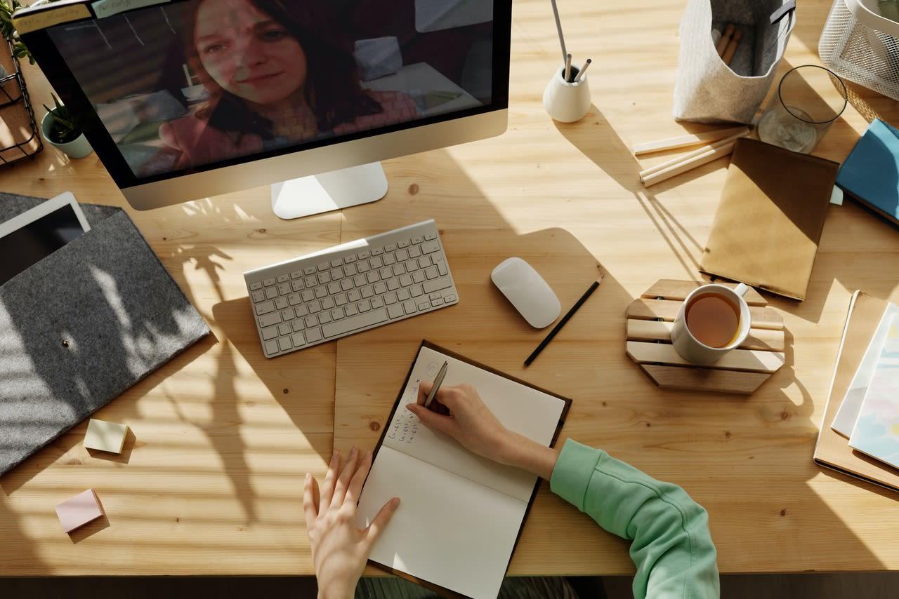 Zu sehen ist ein sonniger Arbeitsplatz am Holzschreibtisch mit einem offenen Zoom-Meeting.