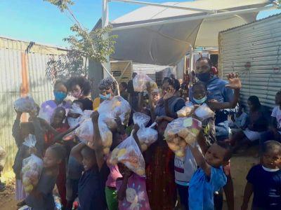Die Kinder halten glücklich Pakete mit Äpfeln, Mehl und Maispulver in die Luft.