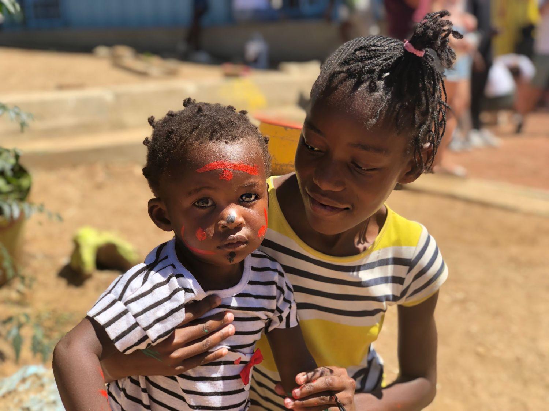 Eine große Schwester hält ihren kleinen Bruder stolz in die Kamera. Der kleine hat rote Farbe im Gesicht.