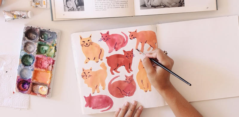 person drawing cats in sketchbook