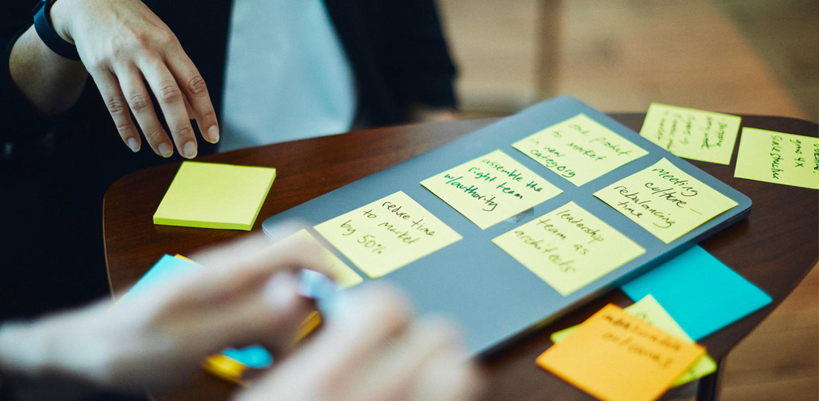 person writing OKRs on sticky notes, person writing OKRs on post-it notes