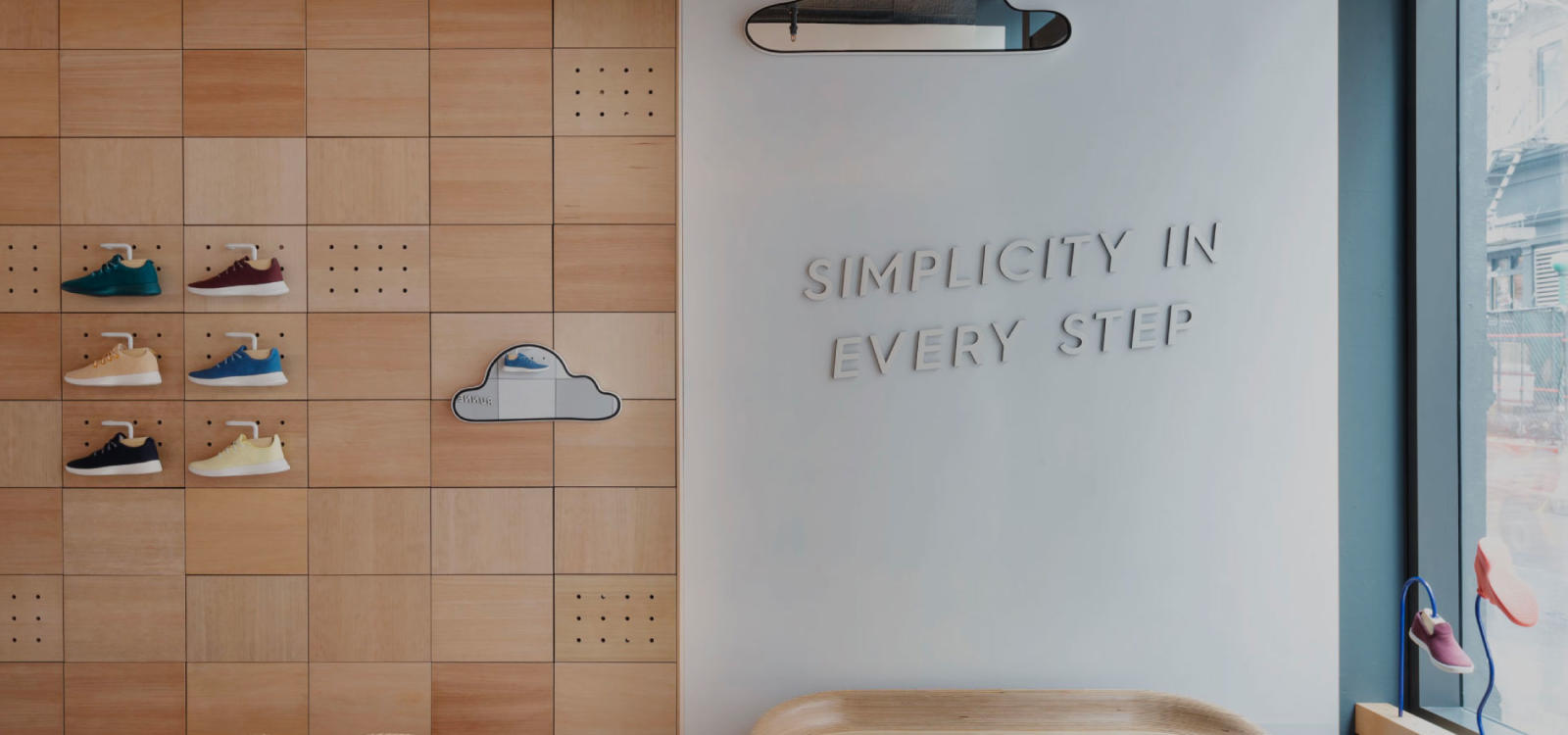 wall in allbirds shop that says 'simplicity in every step', shoe display