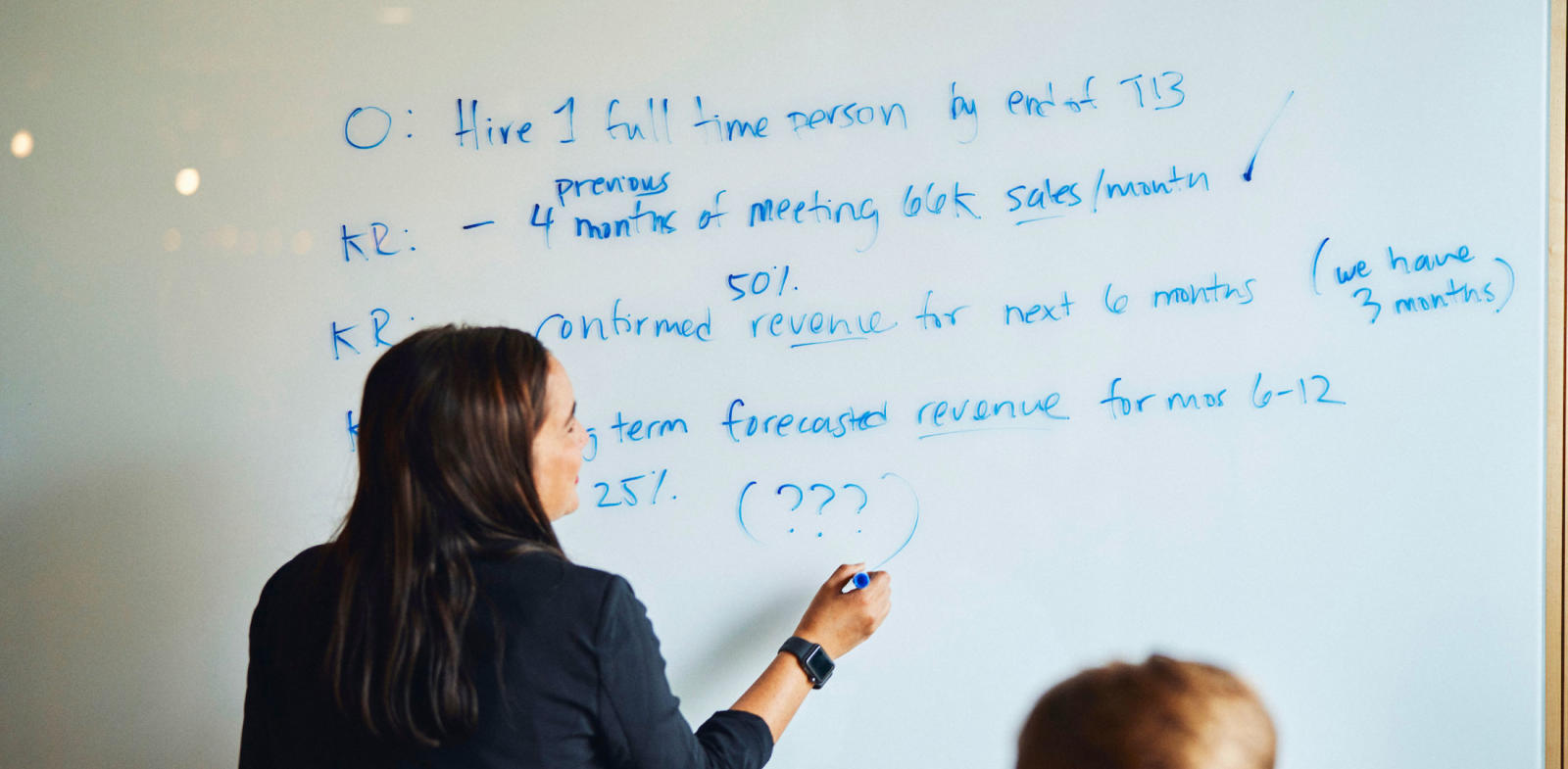woman writing OKRs on whiteboard