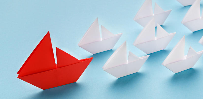 red paper boat leading white paper boats on a blue background, marketing okrs