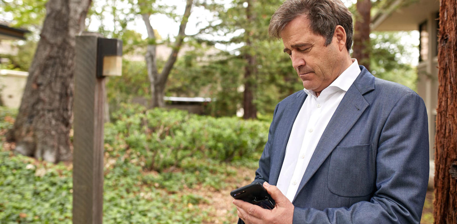 Bing Gordon outdoors looking at mobile phone