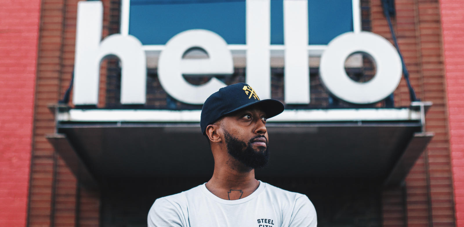 black man standing in front of hello sign