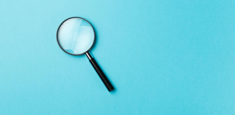 magnifying glass on blue background, finding the why of your company with okrs