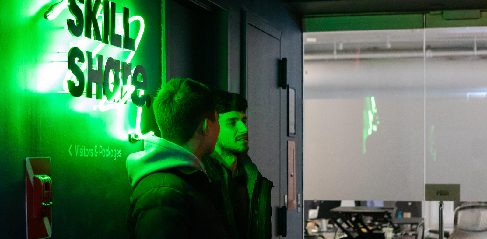 two people talking in front of a skillshare neon sign
