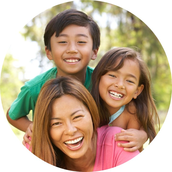 A caregiver and 2 children pose laughing.