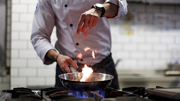 chef with saucepan in kitchen