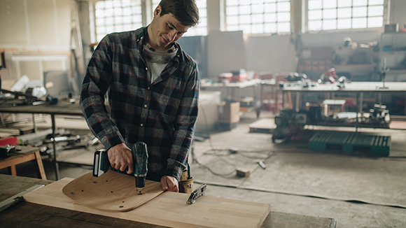 man using drill at workbench