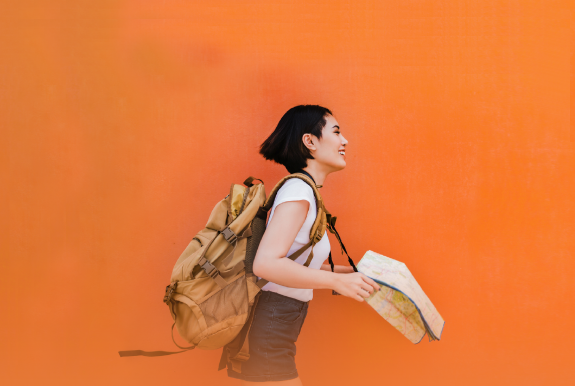 Happy asian woman holding a map and walking in front of orange wall.