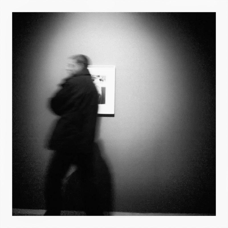 Black and White pinhole-style photo of person passing by a photograph in a gallery.