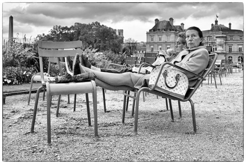 Black and White photo of woman sitting in reclining chair in the Jardins Luxembourg, Paris France