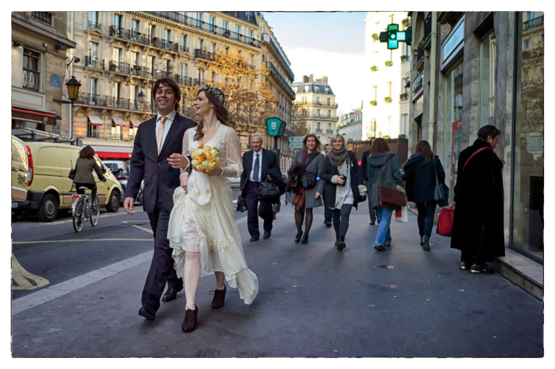 Colour photo of newly married couple walking down Parisien street. The woman is carrying yellow bouquet of flowers.