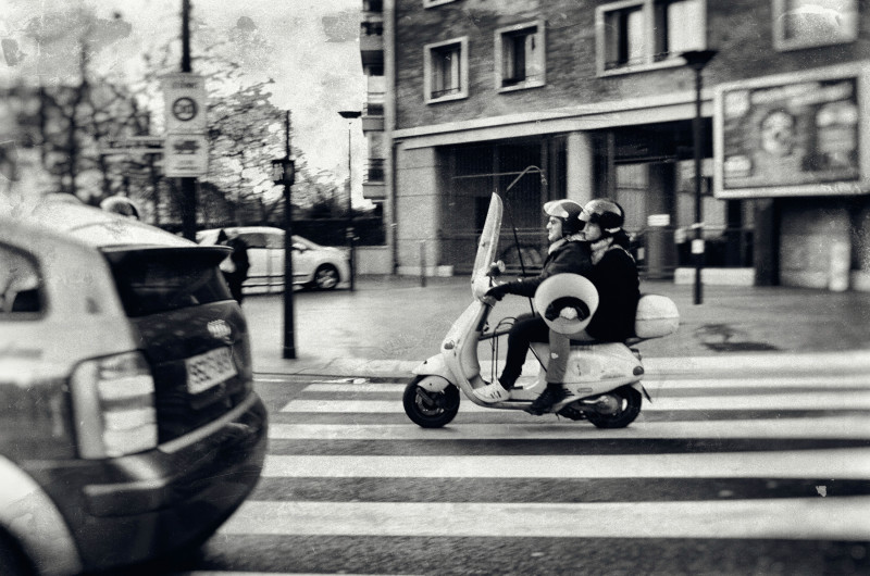 Slightly antique tinted photograph of couple on Moped. The woman is carrying a lamp shade.