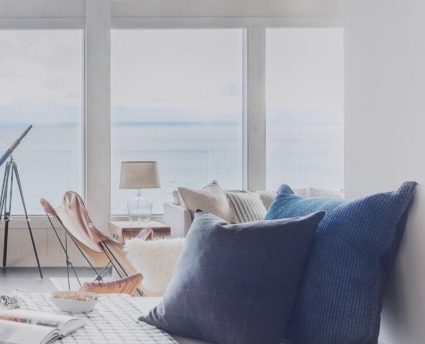 blue pillows on couch with ocean view