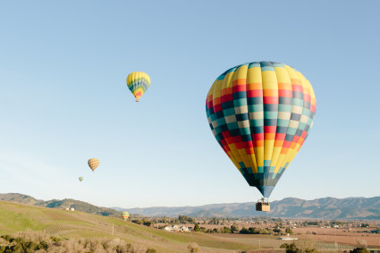 hot air balloons over hills