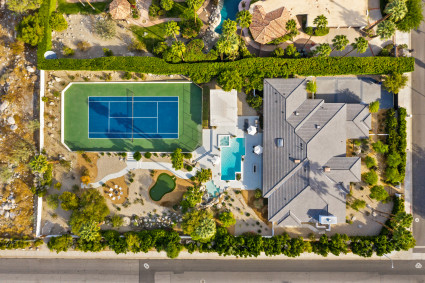 aerial view of palm springs home with pool, golf, and tennis court