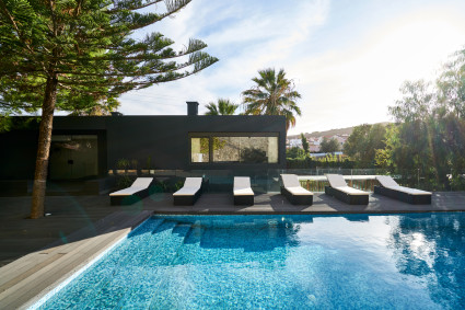 black house with pool and pool chairs