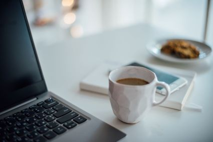 coffee cup on desk with compter and notebook